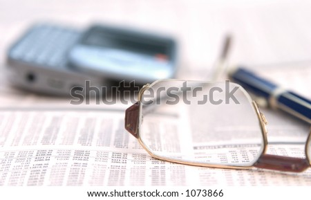 Glasses on a financial newspaper. Mobile phone and a pen in the background.