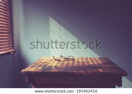 Glasses on desk by window with shadows from blinds