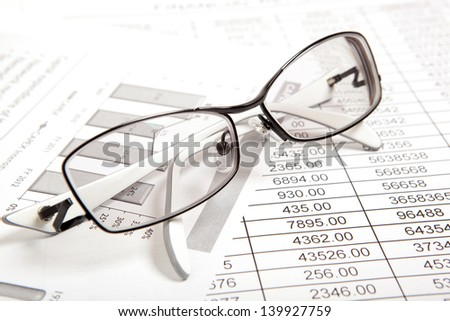 Glasses on paper table with finance report - stock photo