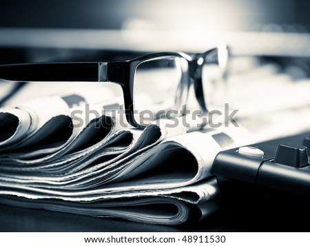 Glasses on stack of newspapers, very shallow focus