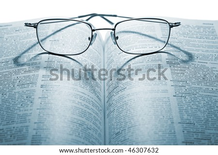 Glasses on the book on the white background