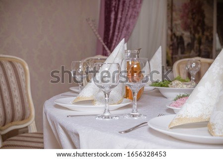 Glasses on the table. Festive table setting. Wedding decor. Table setting in fine art style. Cafe decor. Catering wedding ceremony, selective focus.crystal glasses on the festive table.linen napkins