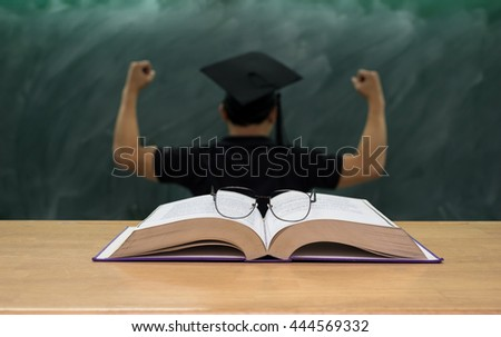 Glasses over the Books on the desk in class room with the man who wear the graduation cap over the black board background,Education concept