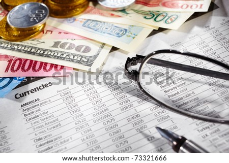 Glasses over the foreign exchange sheet with money from different countries on edge - stock photo