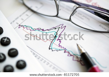 Glasses, pen and calculator on stocks and shares financial graph