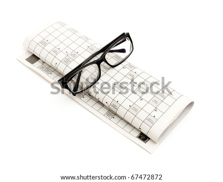 Glasses, pen over mutual funds data on newspaper