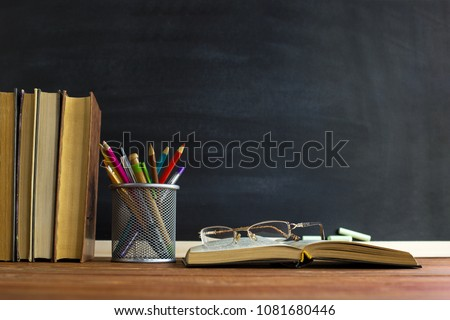 Photo of Glasses teacher books and a stand with pencils on the table, on the background of a blackboard with chalk. The concept of the teacher's day. Copy space.