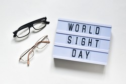 Glasses that correct eyesight and light box with text WOLD SIGHT DAY on a white background. Flat lay. Holiday concept.