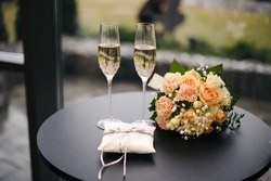 Glasses, wine, a bouquet and wedding rings. Wedding holiday attributes. Shallow depth of field.