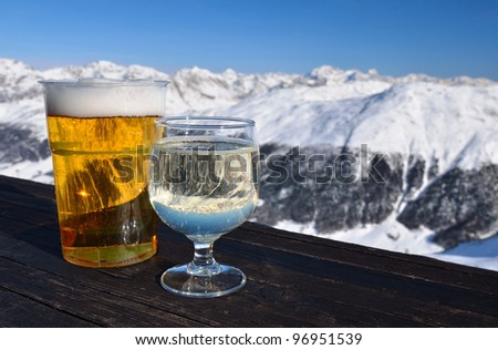 Glasses with beer and white wine on a wooden table in high mountain cafe. Shallow depth of field.