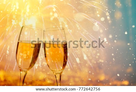 Glasses with champagne against fireworks and holiday lights - Celebrating the New Year #772642756