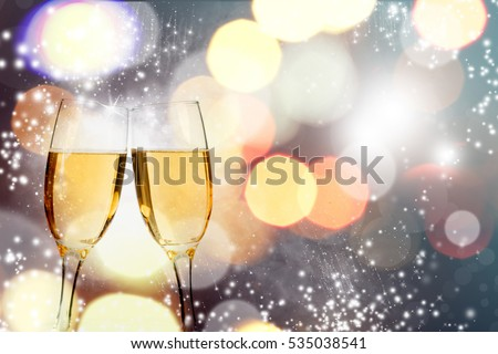 Glasses with champagne against fireworks holiday lights - Celebrating New Year #535038541