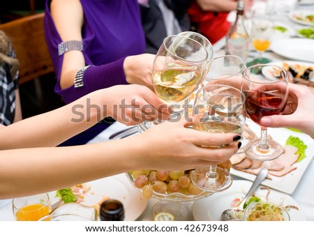 glasses with champagne and red wine in female hands being clinked during drinking toast
