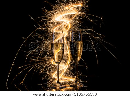 Glasses with champagne in the bright light of Bengal lights. Black background. The concept of celebration and celebration. New Year, Christmas, wedding. #1186756393