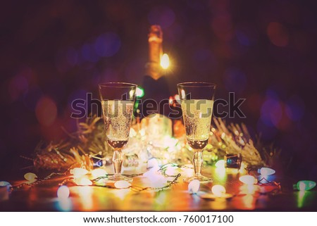 glasses with champagne stand on a wooden table against the background of lights of a garland. two glasses of champagne toasting against bokeh lights background #760017100