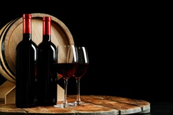 Glasses with delicious wine, bottles and barrel on table against dark background