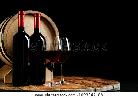 Glasses with delicious wine, bottles and barrel on table against dark background #1093542188