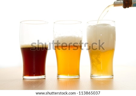glasses with different beers on a white background