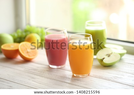 Glasses with different juices and fresh fruits on wooden window sill