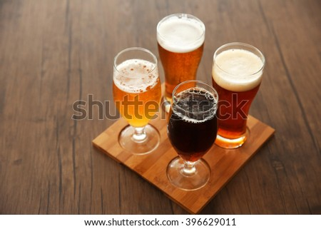 Glasses with different sorts of craft beer on wooden tray