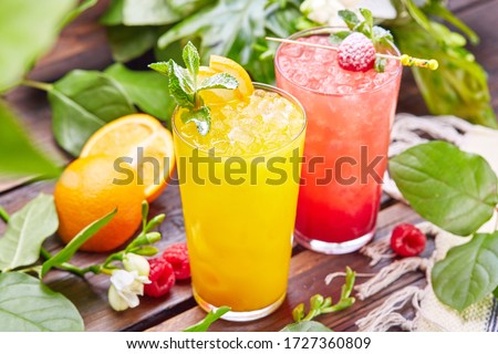 Glasses with fresh lemonade in summer greenery and flowers on the background of a wooden table, citrus and berry lemonade with frappe ice on a wooden table top on the background of a summer garden