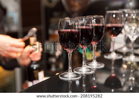 glasses with red wine on bar counter