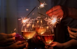 glasses with sparkling wine and sparkler is held by a company of people