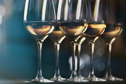 Glasses with white wine on blurred background