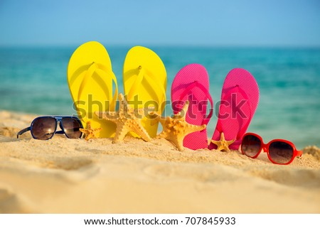 Glasses with yellow and pink sandals stand in the sand against the background of the sea - Shutterstock ID 707845933