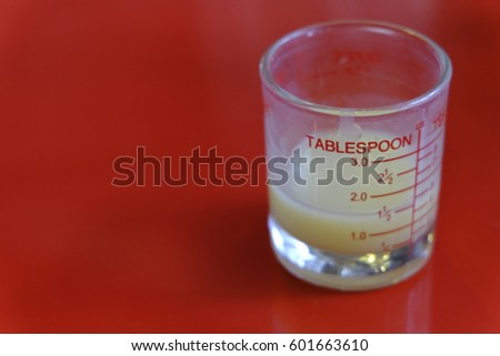 Glassware measure milk tablespoon on red color table. #601663610