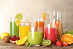 Glassware with different juices and fresh fruits on table