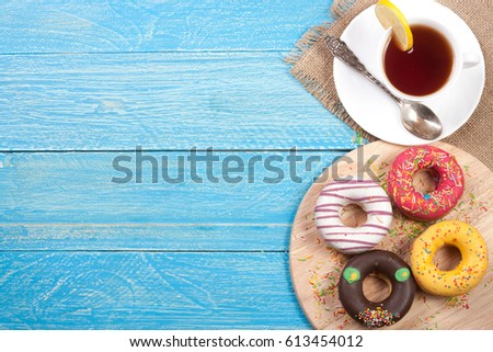 glazed donuts with a cup of tea on a blue wooden background with copy space for your text. Top view #613454012