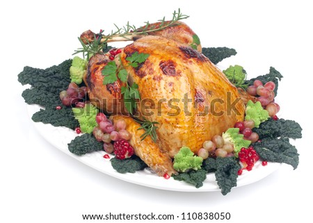 Glazed roasted turkey garnished with grapes, pomegranates, and broccoli over white background