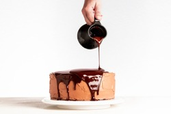 Glazing chocolate cake with melted chocolate. Woman pouring chocolate over cake. Homemade cocoa layered cake. Birthday cake and dripping chocolate.