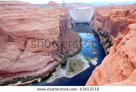 Glen canyon dam harnesses electricity from the Colorado River and forms the border of Lake Powell.  Tall, sheer, orange colored canyon walls tower over the river, forming great viewpoints