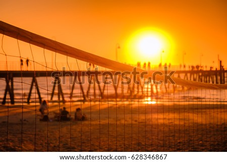 Glenelg beach at sunset viewed across valleyball net, South Australia