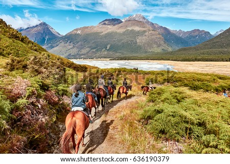 Glenorchy, New Zealand - Feb 07, 2017: Tourist embark on a Horse Riding on a farm in Glenorchy, NZ. it was used as one of the settings in Lord of the Rings films.                                #636190379