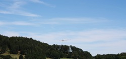 glider on a background of the blue sky in the mountains flying over the trees