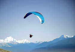 glider paragliding over snowy mountain peaks flying  adrenaline and freedom concept