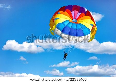 Gliding using a parachute on the background of cloudy blue sky. Stock fotó ©