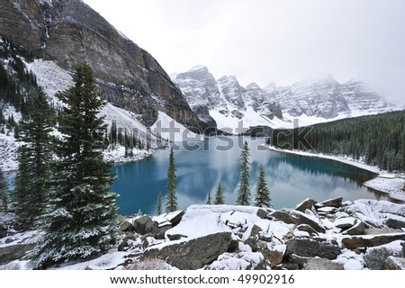 Glimmering crystal sapphire blue of Moraine Lake framed with ten snow peaks standing white-gray in morning fog Banff #49902916