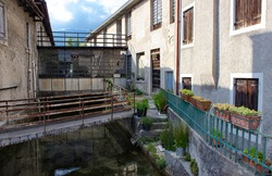 Glimpse of the old town houses in Vittorio Veneto, Italy and a small abandoned factory. The bridge with the rusty handrail crosses the canal. On the stairs there are pots with spontaneous plants.