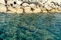 Glistening transpatent aquamarine sea water and  white rocks