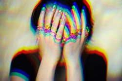 Glitched portrait of a woman hidding her face. Glitch art.