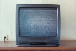 glith television analog signal on tv screen on wooden stand closeup front view