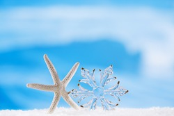 glitter christmas glass snowflake with starfish  on  beach with seascape background