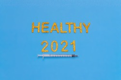 Glitter golden letters and numbers on a blue background. Healthy 2021. Anti covid concept. Vaccine symbolic concept.