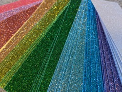 Glitter rainbow cardstock fanned out and ready for crafting