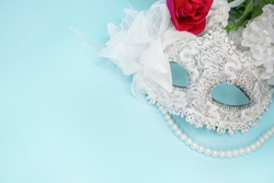 Glitter venetian lace mask on light blue background, with red rose, white flower and pearl necklace. Carnival, Mardi Gras concept.