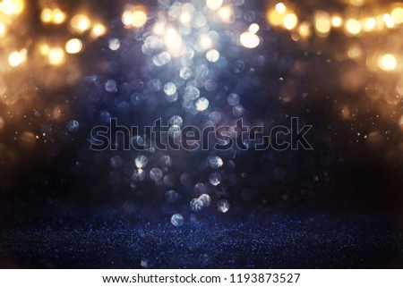 glitter vintage lights background. black, gold and blue. de-focused